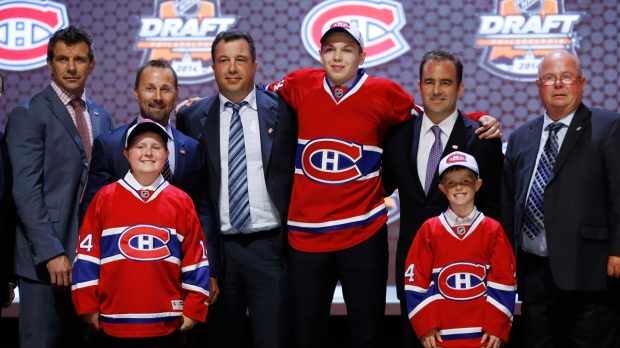 Nikita Scherbak stands with Montreal Canadiens officials after being chosen 26th overall during the first round of the NHL hockey draft, Friday, June 27, 2014, in Philadelphia. (AP Photo/Matt Slocum)