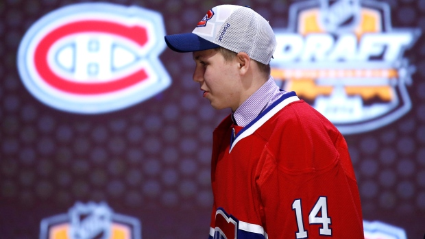 Nikita Scherbak walks off the stage after being chosen 26th overall by the Montreal Canadiens during the first round of the NHL hockey draft, in Philadelphia, on Friday, June 27, 2014. (AP Photo/Matt Slocum)