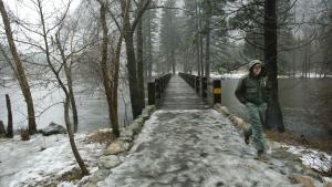 Park Ranger Cullen Tucker walks across a bridge during a rain storm on the Merced River in Yosemite National Park, Calif., Sunday, Jan. 8, 2017. (AP / Gary Kazanjian)