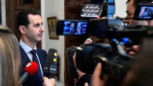 Syrian President Bashar Assad, left, speaks with French journalists in Damascus, Syria, on Jan. 9, 2017. (SANA via AP)