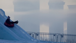 A woman slides down the hill as residential buildings are shrouded in cold mist, in Moscow, Russia, on Jan. 9, 2017. (Ivan Sekretarev / AP)