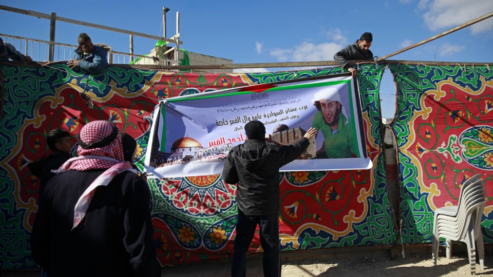 Palestinians hang a banner at a mourning tent being set up for Fadi Qunbar, in east Jerusalem, Monday, Jan. 9, 2017. (Mahmoud Illean / AP)