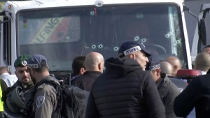 This frame grab from video, shows an Israeli emergency services personnel in front of the truck, with bullet holes in the windshield, that was used in an attack that killed at least four people in Jerusalem, on Jan. 8, 2017. (AP)