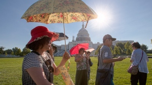 Visitors from Korea shield themselves from the early morning sun as they tour the Capitol in Washington, on Aug. 12, 2016. (J. Scott Applewhite / AP)