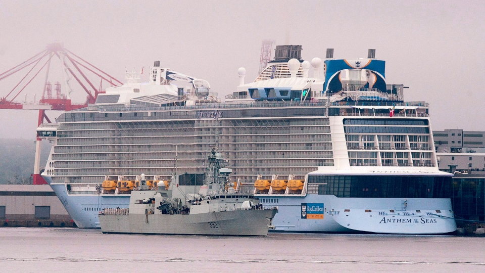 The massive cruise ship Anthem of the Seas, operated by Royal Caribbean International, dwarfs HMCS Ville de Quebec, a Halifax-class frigate, in Halifax on Thursday, Sept. 1, 2016. (THE CANADIAN PRESS/Andrew Vaughan)