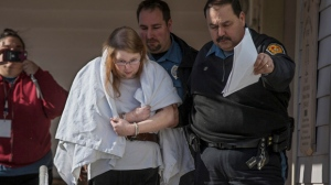 Sara Packer, center, handcuffed, the adoptive mother of Grace Packer, was led out of District Court in Newtown, Pa., Sunday, Jan. 8, 2017, by Pennsylvania Constables and taken into custody. (Michael Bryant/The Philadelphia Inquirer via AP)