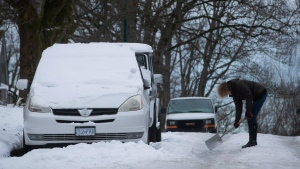 A woman uses a metal shovel to chip away at the ice built up on a street in Vancouver, B.C., on Friday January 6, 2017. THE CANADIAN PRESS/Darryl Dyck