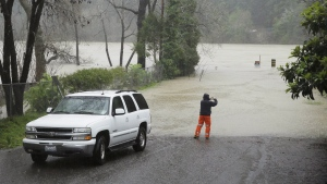 A man stops to take a picture of the Russian River as it floods Johnson's Beach Tuesday, Jan. 10, 2017, in Guerneville, Calif. (AP / Eric Risberg)