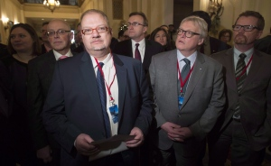 Manitoba Health Minister Kelvin Goertzen, (centre left), Quebec Health Minister and Social Services Minister Gaetan Barrette (centre right) and other provincial health ministers wait to speak as a group before a meeting with the federal finance and health ministers in Ottawa, Monday December 19, 2016. (THE CANADIAN PRESS/Adrian Wyld)