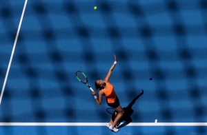 Shelby Rogers of the United States serves to Romania's Simona Halep during their first round match at the Australian Open tennis championships in Melbourne, Australia, Monday, Jan. 16, 2017. (AP Photo/Aaron Favila)