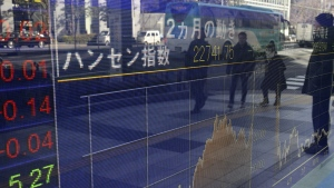 People are reflected on the electronic board of a securities firm in Tokyo on Monday, Jan. 16 2017. (AP / Koji Sasahara)