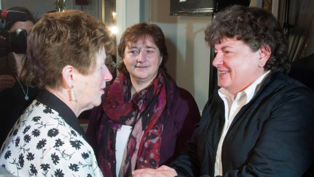 Plaintiffs Janet Merlo, centre, and Linda Gillis Davidson, right, speak with a woman following an update on RCMP harassment related litigation in Ottawa, Thursday October 6, 2016. (THE CANADIAN PRESS/Adrian Wyld)