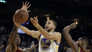 Golden State Warriors' Stephen Curry, centre, lays up a shot between Cleveland Cavaliers' Iman Shumpert, left, and Tristan Thompson during the second half of an NBA basketball game in Oakland, Calif. on Monday, Jan. 16, 2017.  (AP / Ben Margot)