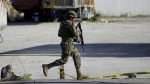 A soldier runs near the state prosecutors' office after gunmen opened fire on the building in Cancun, Mexico on Tuesday, Jan. 17, 2017. (AP)