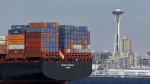 In this Feb. 15, 2015, file photo, the Space Needle towers in the background beyond a container ship anchored in Elliott Bay near downtown Seattle. (AP / Elaine Thompson, File)