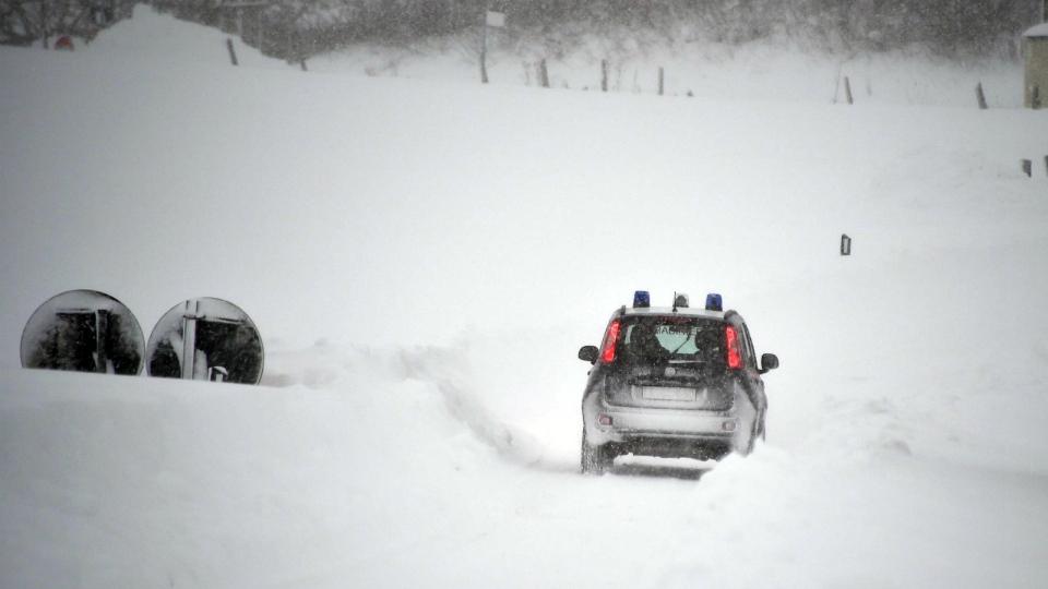 A Carabinieri (Italian paramilitary police) car makes its way through snow in Amatrice, central Italy on Wednesday, Jan. 18, 2017. (Emiliano Grillotti / ANSA)