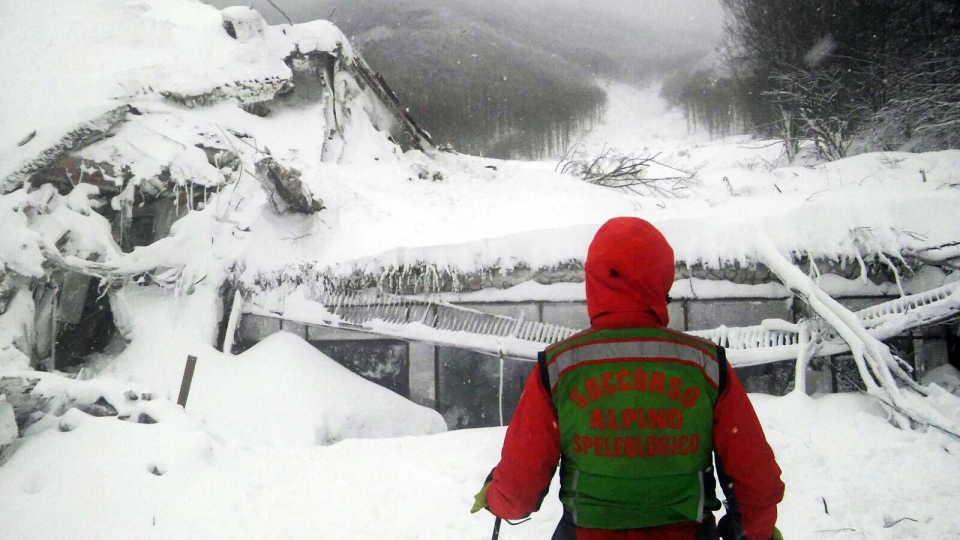 A rescuer stands in front of the Rigopiano Hotel hit by an avalanche in Farindola, Italy, early Thursday, Jan. 19, 2017. (Corpo Nazionale Soccorso Alpino e Speleologico/The National Alpine Cliff and Cave Rescue Corps (CNSAS) via AP)