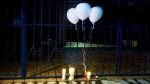 Balloons and candles stand at the entrance of the American School of the Northeast after a school shooting in Monterrey, Mexico, Wednesday, Jan. 18, 2017. (AP Photo/Emilio Vazquez)