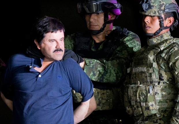 In this Jan. 8, 2016 file photo, a handcuffed Joaquin 'El Chapo' Guzman is made to face the press as he is escorted to a helicopter by Mexican soldiers and marines at a federal hangar in Mexico City. (AP / Eduardo Verdugo)