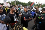In this Aug. 15, 2016 file photo, Memphis police department Lieutenant A. Gardner, center right, talks with a protester, Antonio Blair, centre left, during a protest at Graceland's Elvis Candelight Vigil in Memphis, Tenn. (Nikki Boertman/The Commercial Appeal via AP)