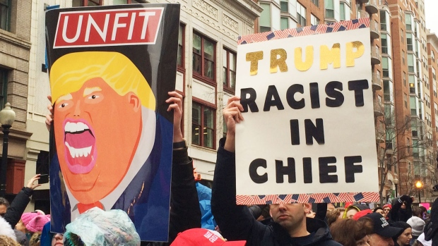 Protesters hold up signs ahead of the inauguration of U.S. President-elect Donald Trump. (Mark Khouzam/CTVNews)