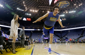 In this Jan. 12, 2017 photo, Golden State Warriors forward Anderson Varejao, right, demonstrates a yoga position while posing for photographs as yoga instructor and Warriors director of corporate communications Lisa Goodwin watches before an NBA basketball game between the Warriors and the Detroit Pistons in Oakland, Calif. (AP / Jeff Chiu)