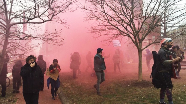 Protesters run away from tear gas in Washington on inauguration day for Donald Trump, Friday, Jan. 20, 2017. (Richard Madan / CTVNews)
