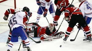 New Jersey Devils goalie Keith Kinkaid, center, eyes the puck while defending his net against the Montreal Canadiens during the third period of an NHL hockey game, Friday, Jan. 20, 2017, in Newark, N.J. The Canadiens won 3-1. (AP / Julio Cortez)