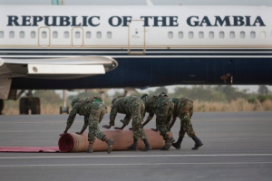 Soldiers roll back the red carpet near a parked Gambian Presidential aircraft on the tarmac of Banjul's airport Friday Jan. 20, 2016. (AP / Jerome Delay)