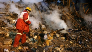 An Iranian aid worker with a sniffer dog searches among the remains of the Plasco building which was engulfed by a fire and collapsed on Thursday, in central Tehran, Iran, Saturday, Jan. 21, 2017.  (AP Photo/Ebrahim Noroozi)