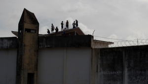 Inmates stands on the roof of a building amid tension between rival gangs in the Alcacuz prison in Nisia Floresta, near Natal, Brazil, Friday, Jan. 20, 2017. (AP Photo/Felipe Dana)
