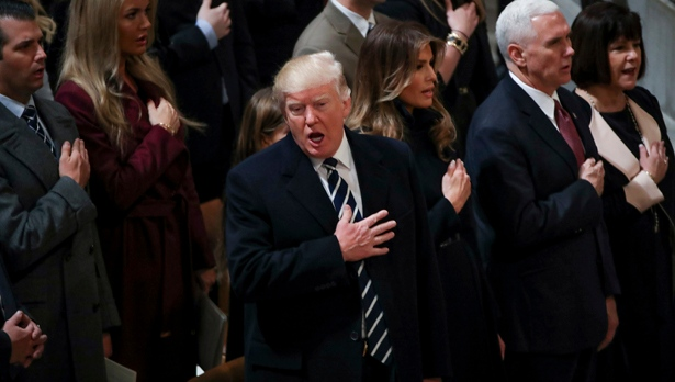 President Donald Trump signs the National Anthem during a National Prayer Service at the National Cathedral, in Washington, Saturday, Jan. 21, 2017., Also pictured is Donald Trump Jr., left, his wife Vanessa Trump, second from left, first lady Melania Trump, third from right, Vice President Mike Pence, second from right, and his wife Karen Pence, right. (AP Photo/Manuel Balce Ceneta)