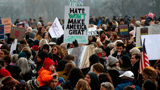 Protesters carrying banners and placards take part in a Women's March next to the Eiffel Tower, in Paris, France, Saturday, Jan. 21, 2017. The march is part of a worldwide day of actions following the inauguration of U.S President Donald Trump. (AP Photo/Christophe Ena)