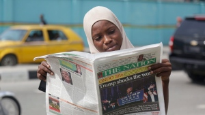 """A muslim woman reads a newspapers on a street reporting with headline """"Trump shocks the world"""" to refer to U.S President-elect Donald Trump's victory in Lagos, Nigeria, Thursday, Nov. 10, 2016. (AP Photo/Sunday Alamba)"""
