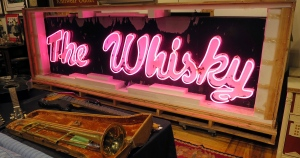 In this Friday, Jan. 20, 2017 photo, a marquee from the legendary Los Angeles rock 'n' roll club, Whisky a Go Go, glows at the Saco River Auction Co., in Biddeford, Maine. (AP / David Sharp)