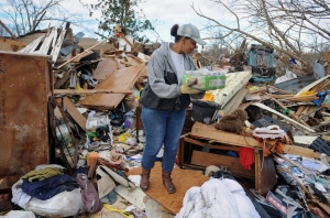 A volunteer helps salvage a Hall Avenue resident's personal belongings as cleanup continued in the Hattiesburg, Miss., neighborhoods that were destroyed from Saturday's twister Sunday, Jan. 22, 2017.  (Ryan Moore/WDAM-TV via AP)