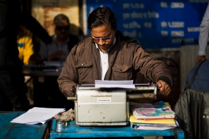 In this Jan. 18, 2017 photo, a roadside professional typist works near Delhi's stock exchange market in New Delhi, India. (AP / Bernat Armangue)