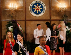 Miss Universe contestants, from left in foreground, Zuzana Kollarova of The Slovak Republic, Cheryl Chou of Singapore and Hawa Kamara of Sierra Leone, walk back to their seats after posing with Philippine President Rodrigo Duterte, in background, during their courtesy call at Malacanang Palace Monday, Jan. 23, 2017 in Manila, Philippines. Eighty-six candidate are vying for the title in the grand coronation Jan. 30 to succeed Pia Wurtzbach of the Philippines. (AP / Bullit Marquez)