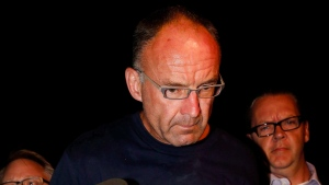 Douglas Garland is escorted into a Calgary police station in connection with the disappearance of Nathan O'Brien and his grandparents in Calgary, Alta., on July 14, 2014. (Jeff McIntosh/The Canadian Press)
