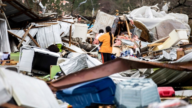 A woman holds a child while walking through a farm that was damaged by a tornado in Adel, Ga., on Sunday, Jan. 22, 2017. (AP Photo/Branden Camp)