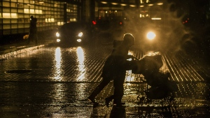 A woman pushes a baby stroller as she walks against heavy wind in the rain in the Brooklyn borough of New York, Monday, Jan. 23, 2017. (AP / Andres Kudacki)