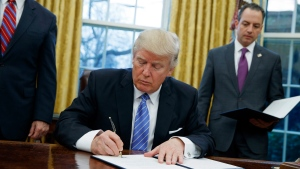 President Donald Trump signs an executive order to withdraw the U.S. from the 12-nation Trans-Pacific Partnership trade pact agreed to under the Obama administration in the Oval Office of the White House in Washington on Jan. 23, 2017. (Evan Vucci/AP)