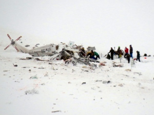 Rescuers work next to a helicopter that crashed in the Campo Felice ski area, central Italy, Tuesday, Jan. 24, 2017. A helicopter ferrying an injured skier off the slopes crashed Tuesday into a mountainside in central Italy, killing all six people aboard in the latest tragedy to hit a region slammed by recent earthquakes, heavy snowfall and an avalanche, officials said. (Claudio Lattanzio/ANSA via AP)