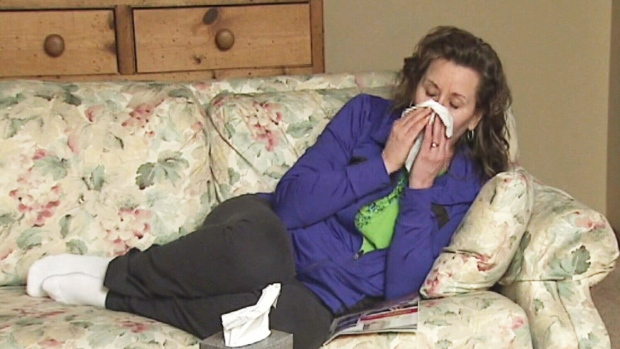 In this undated file photo, a woman suffers through a cold at home.