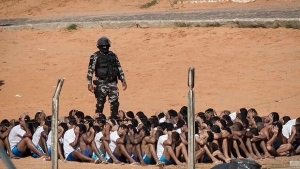 A Military Police officer stands next to inmates during a head count in the Alcacuz prison in Nisia Floresta, near Natal, Brazil, Tuesday, Jan. 24, 2017.  (AP Photo/Felipe Dana)