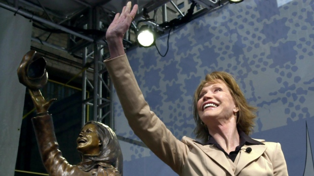 Mary Tyler Moore is mirrored by a bronze statue of herself as she waves to a helicopter flying overhead after the unveiling of the statue capturing her flinging her tam in Minneapolis on Wednesday, May 8, 2002. A crowd of about 2,000 gathered for the unveiling at the intersection in downtown Minneapolis where Moore originally twirled in the opening for her 1970's television hit, 'The Mary Tyler Moore Show.' (AP Photo / Ann Heisenfelt)