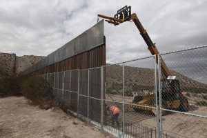In this Nov. 10, 2016 file photo, workers raise a taller fence along the Mexico-US border between the towns of Anapra, Mexico and Sunland Park, New Mexico. (AP Photo/Christian Torres, File)