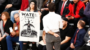 Prime Minister Justin Trudeau speaks with pipeline protestors as they stand and hold signs at a town hall at the University of Winnipeg in Winnipeg, Thursday, Jan. 26, 2017. THE CANADIAN PRESS/John Woods