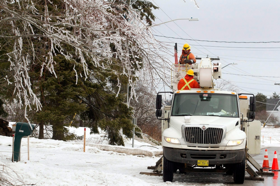 Workers tend to hydro poles near Moncton, N.B., on Thursday, Jan. 26, 2017. (THE CANADIAN PRESS/Ron Ward)