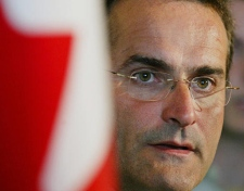 Jean Lapierre, standing beside a Canadian flag, fields questions in Halifax on August 5, 2005. (CP / Andrew Vaughan)